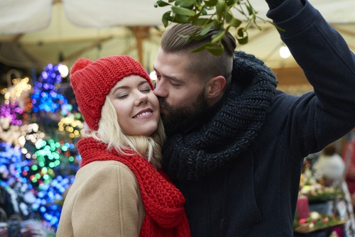 couple kissing underneath mistletoe