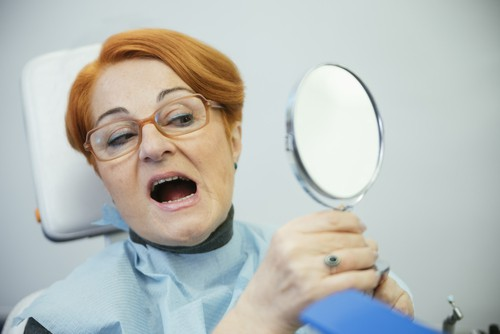 woman in dental chair looking at mouth in mirror