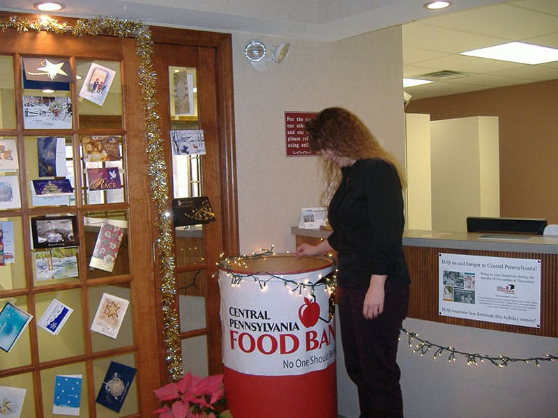 woman standing next to Central Pennsylvania Food Bank donation barrel