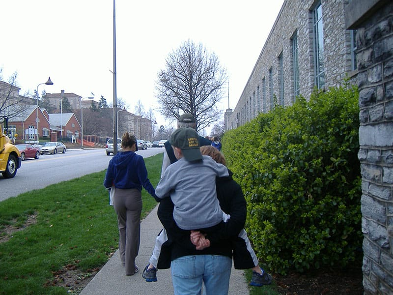 woman giving small boy a piggy back ride