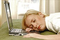 Woman sleeping next to laptop