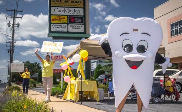 tooth mascot and people standing happily with signs at lemonade stand