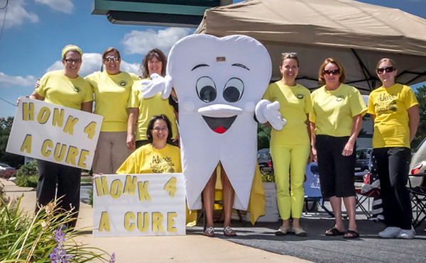 group of people standing with tooth mascot
