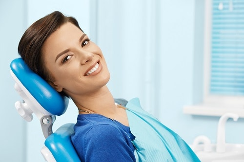woman smiles in dental chair